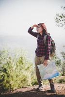 chica viajera buscando la dirección correcta en el mapa mientras camina por la montaña