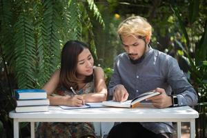 Education couple sitting at nature home garden reading for exam together