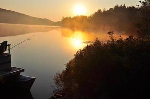 The sun rising over a misty lake with boat in water