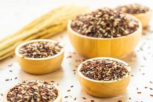 Raw brown rice in wooden bowl photo