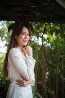La empresaria sonriendo mientras está de pie en el jardín de su casa