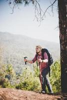 Man traveler with backpack looking at the map while mountaineering photo