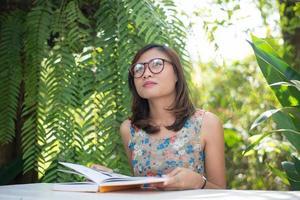 Mujer joven inconformista leyendo libros en el jardín de su casa con la naturaleza foto