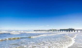 Wooden dock with ocean waves at Daytona Beach, Florida photo