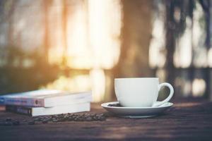 Taza de café con pila de libros sobre fondo natural por la mañana