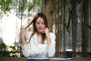 Young businesswoman stretching herself and yawning at workplace photo