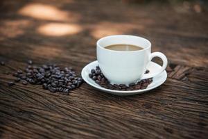 Taza de café y granos de café en la mesa de madera