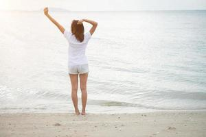 Rear of young woman standing stretch her arms in the air on the beach with bare feet photo