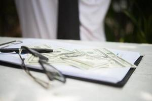 Close-up of white table with document, glasses, pen and dollar bill photo