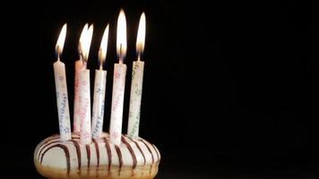 Velas de cumpleaños de seis años en un donut glaseado
