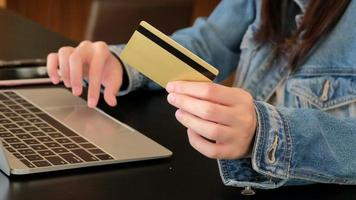 Woman holding credit card using computer for online shopping video