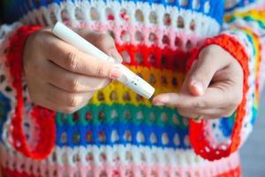 Mujer joven midiendo su nivel de glucosa en casa foto