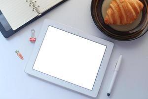 maqueta de tableta con desayuno en el escritorio foto
