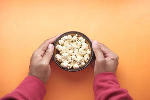 tazón de palomitas de maíz sobre fondo naranja foto