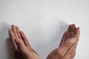 La mano de un joven cuidando una forma de corazón escrita a mano con un lápiz foto