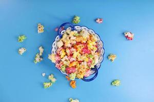 Palomitas de maíz de colores en un recipiente sobre fondo azul. foto