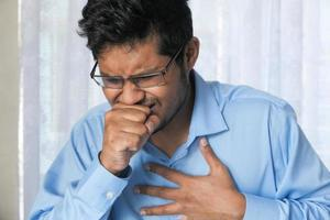 Young man coughing photo