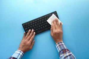 manos limpiando un teclado