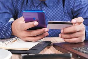 Mano de hombre sosteniendo tarjeta de crédito y usando teléfonos inteligentes para compras en línea