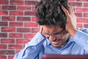hombre sosteniendo la cabeza en frustración foto
