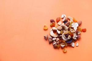 Cerca de muchos frutos secos sobre fondo naranja foto