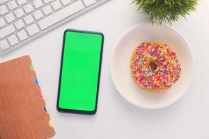 Vista superior del teléfono inteligente y donut en el escritorio foto
