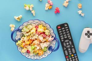 Colorful popcorn with remote and controller on blue background photo