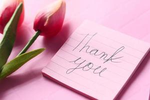 Mensaje de agradecimiento con flor de tulipán sobre fondo rosa