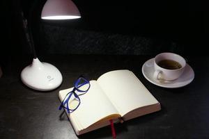 Abra el bloc de notas y la lámpara de mesa por la noche. foto