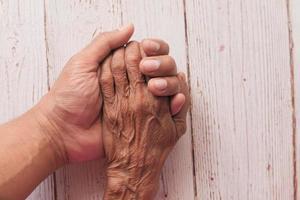 anciano y joven tomados de la mano foto