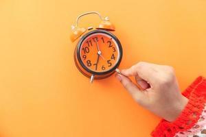 Woman's hand holding alarm clock on orange background photo