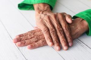 Las manos de la persona mayor aisladas en la mesa blanca foto