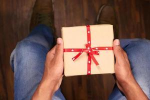 hombre sosteniendo caja de regalo foto