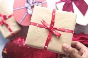 Vista superior de la mano del hombre sosteniendo una caja de regalo en la mesa