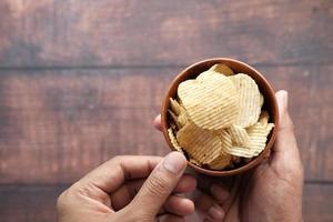 Vista superior de la mano del hombre comiendo papas fritas