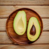 Fresh avocado on a wooden plate