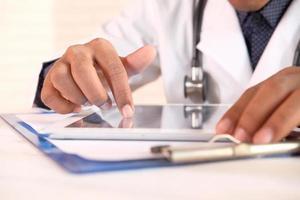 doctor en bata blanca está usando una tableta digital foto