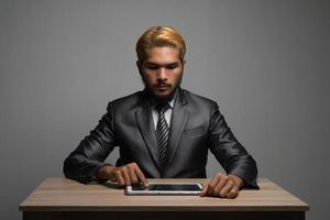 Businessman touching on digital tablet and looking on a blank screen photo