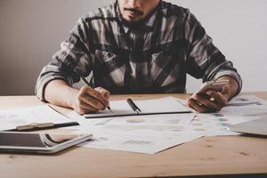 Joven empresario escribe en un cuaderno mientras trabaja en análisis de datos empresariales en la oficina
