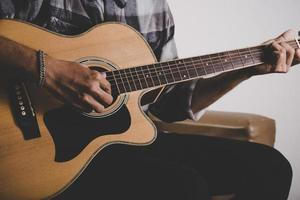 Cerca de barba hipster mano tocando la guitarra foto