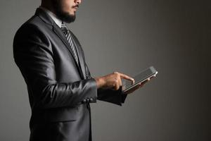Businessman holding and touching on digital tablet and looking on a blank screen photo