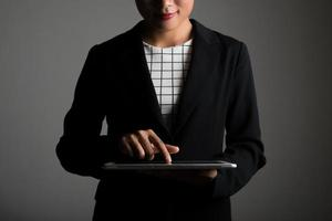 Woman holding and touching on digital tablet and looking on a blank screen photo