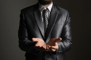 Young businessman presenting a copyspace isolated on black background photo