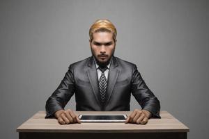 Apuesto joven empresario trabajando con touchpad mientras está sentado en la oficina