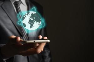 Businessman with smartphone and global network on screen interface