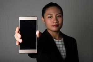 retrato, de, mujer de negocios, actuación, smartphone, contra, fondo negro foto