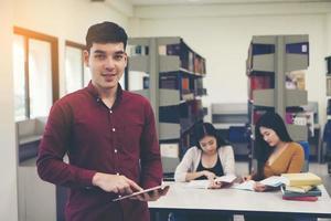 jóvenes estudiantes con tablet pc en la biblioteca foto
