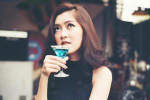 Portrait of a happy young woman having fun and drinking a cocktail photo