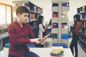jóvenes estudiantes usando tableta en la biblioteca foto