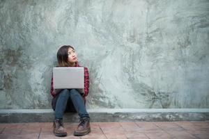 Feliz joven hipster mujer usando su computadora portátil mientras está sentado en el suelo foto